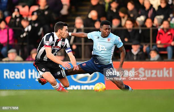 Blackpool's Bright OsayiSamuel is tackled by Grimsby Town's Shaun Pearson during the Sky Bet League Two match between Grimsby Town and Blackpool at...