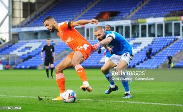 Blackpool's CJ Hamilton shields the ball from Peterborough United's Dan Butler during the Sky Bet League One match between Peterborough United and...