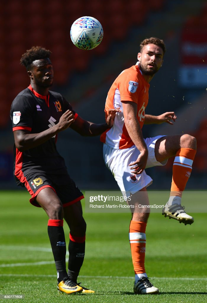Blackpool's Clark Robertson competes with Milton Keynes Dons' Gboly Ariyibi during the Sky Bet League One match between Blackpool and Milton Keynes Dons at Bloomfield Road on August 12, 2017 in Blackpool, England.