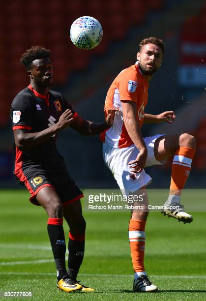 Blackpool's Clark Robertson competes with Milton Keynes Dons' Gboly Ariyibi during the Sky Bet League One match between Blackpool and Milton Keynes...
