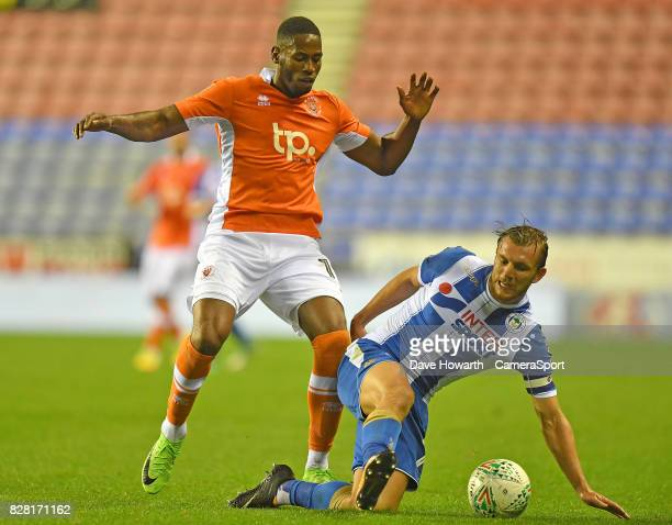 Blackpool's Jamille Matt battles with Wigan Athletic's Alex Gilbey during the Carabao Cup First Round match between Wigan Athletic and Blackpool at...