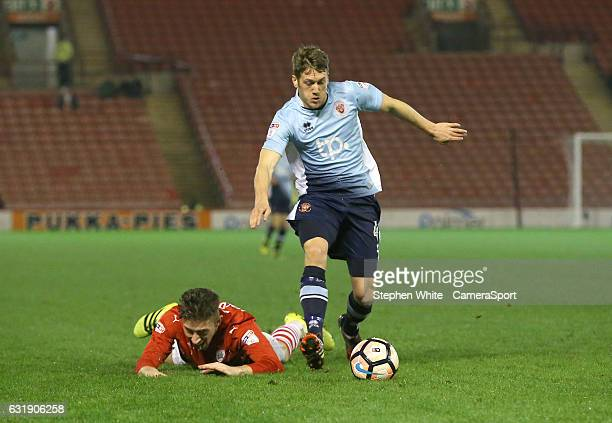 Blackpool's Jim McAlister and Barnsley's Angus MacDonald during the Emirates FA Cup Third Round Replay match between Barnsley and Blackpool at...