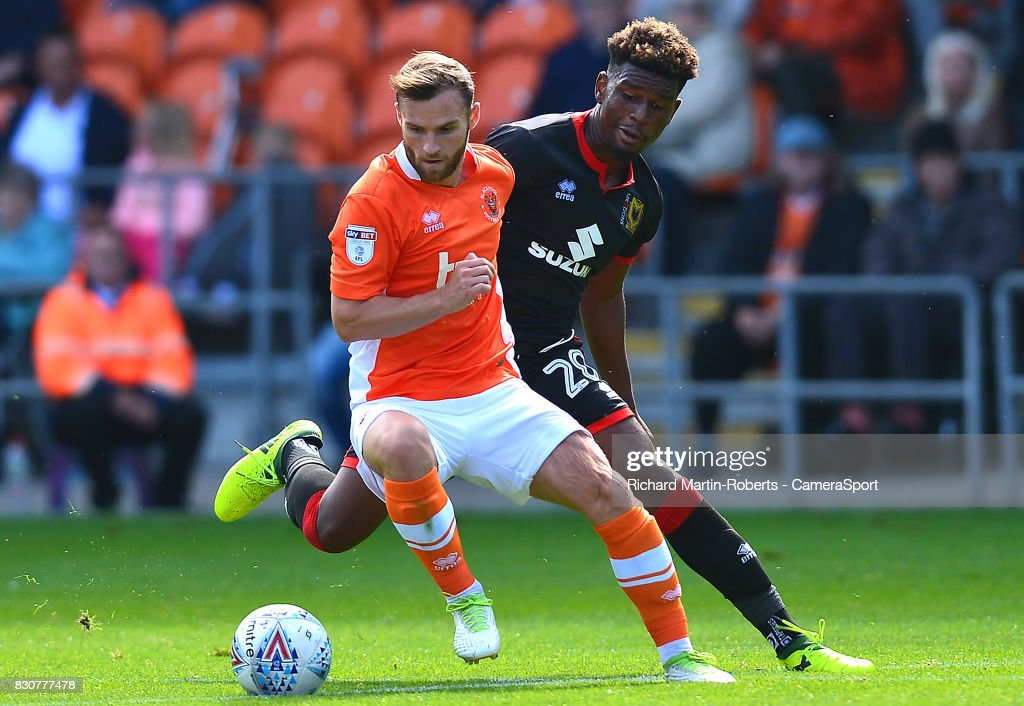 Blackpool's Jimmy Ryan competes with Milton Keynes Dons' Hugo Logan during the Sky Bet League One match between Blackpool and Milton Keynes Dons at Bloomfield Road on August 12, 2017 in Blackpool, England.