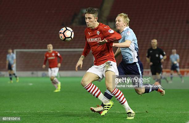 Blackpool's Mark Cullen fights for the ball against Barnsley's Angus MacDonald during the Emirates FA Cup Third Round Replay match between Barnsley...