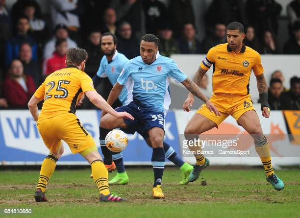Blackpool's Neil Danns under pressure from Newport County's Mark O'Brien during the Sky Bet League Two match between Newport County and Blackpool at...