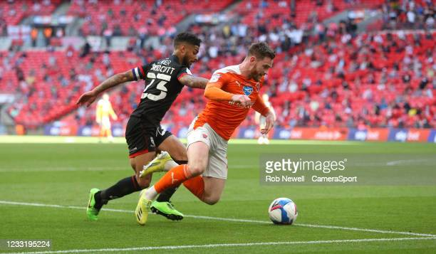 Blackpool's Oliver Turton is taken down by Lincoln City's Liam Bridcutt during the Sky Bet League One Play-off Final match between Blackpool and...