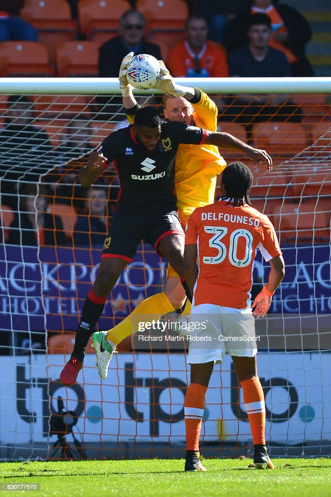 Blackpool's Ryan Allsop claims the ball under pressure from Milton Keynes Dons' Lee Nicholls during the Sky Bet League One match between Blackpool and Milton Keynes Dons at Bloomfield Road on August 12, 2017 in Blackpool, England.