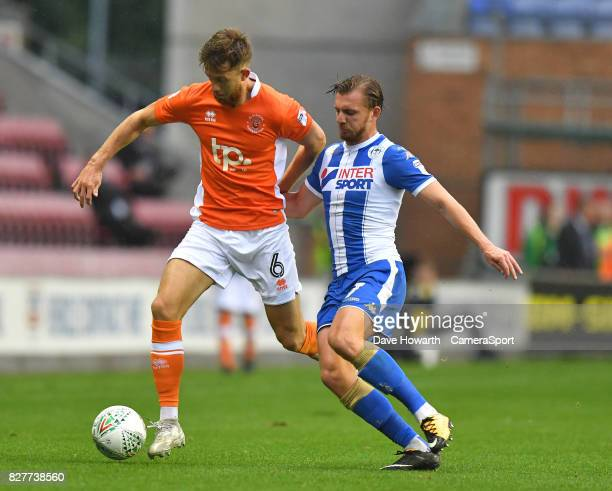 Blackpool's Will Aimson battles with Wigan Athletic's Alex Gilbey during the Carabao Cup First Round match between Wigan Athletic and Blackpool at DW...