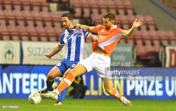 Blackpool's Will Aimson battles with Wigan Athletic's Will Grigg during the Carabao Cup First Round match between Wigan Athletic and Blackpool at DW...