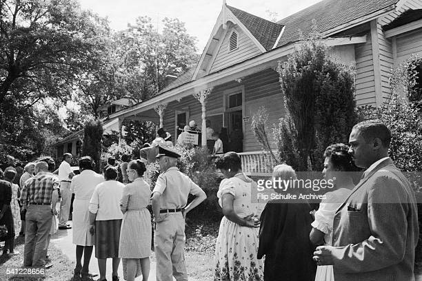 Blacks and whites, for the first time in Alabama, wait in line together to vote after enactment of the Voting Rights Act.
