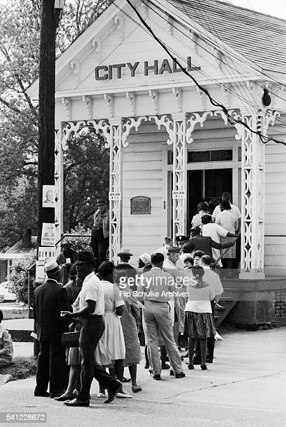 Blacks and whites, for the first time in Alabama, wait in line together to vote at a small town's city hall after enactment of the Voting Rights Act.