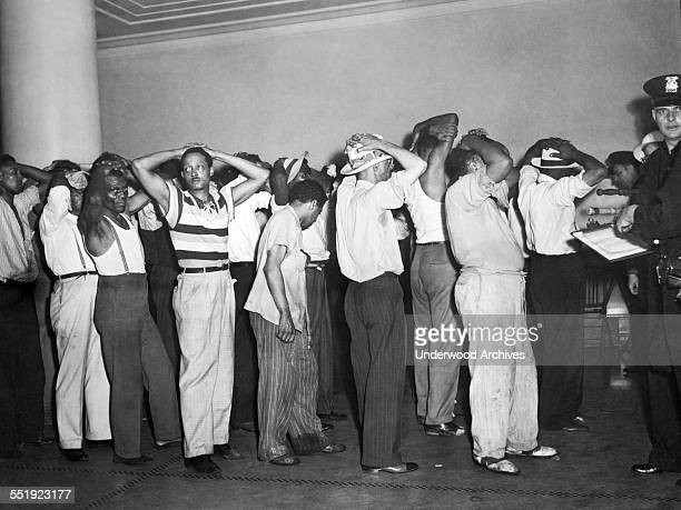 Blacks under arrest being booked into jail by a white police officer in the aftermath of the three days of riots over wartime housing Detroit...