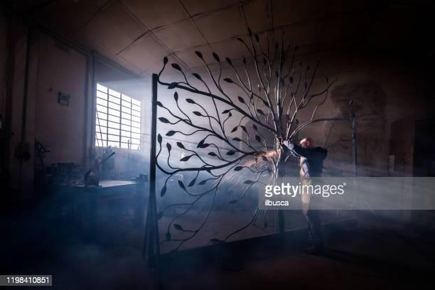 blacksmith artist working in his smithy studio creating a gate-tree - ilbusca foto e immagini stock
