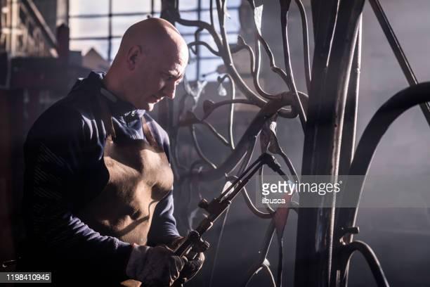 smeden konstnär som arbetar i hans smedja studion skapa en grind-träd - don smith bildbanksfoton och bilder