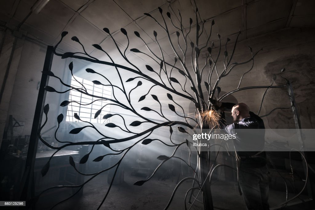 Blacksmith artist working in his smithy studio creating a gate-tree : Stock Photo
