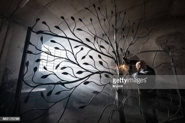 blacksmith artist working in his smithy studio creating a gate-tree - artistic product stock pictures, royalty-free photos & images