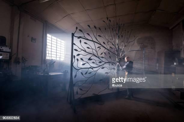 blacksmith artist working in his smithy studio creating a gate-tree - passione foto e immagini stock