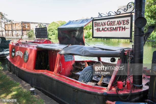 Blacksmith at work on his narrowboat moored on the canal.