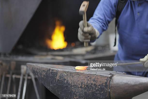 Fabbro ferraio al lavoro con fuoco e a matrice (XL