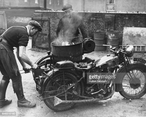 Blacksmith Bill Groom forges a new shoe on the anvil at the back of a mobile smithy on a motorcycle combination, while his brother Tom keeps the...