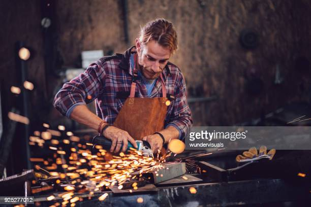 Blacksmith cutting metal with angle grinder in workshop