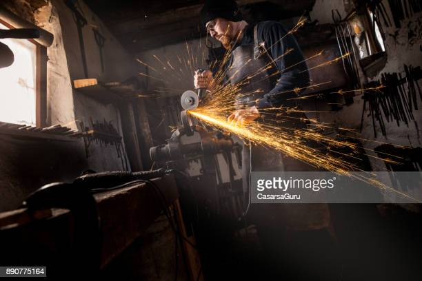 Blacksmith Cutting Scrap Iron with Angle Grinder for his Products, with Sparks Flying