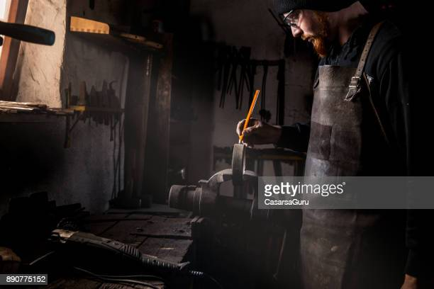 blacksmith drawing cutting lines on a piece of iron for his product - drawing art product stock pictures, royalty-free photos & images