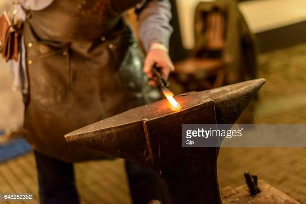 Forjamento de aço quente com um martelo na bigorna de ferreiro