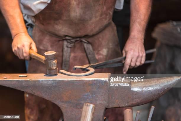 schmied schmieden metall mit werkzeugen - hufeisen stock-fotos und bilder