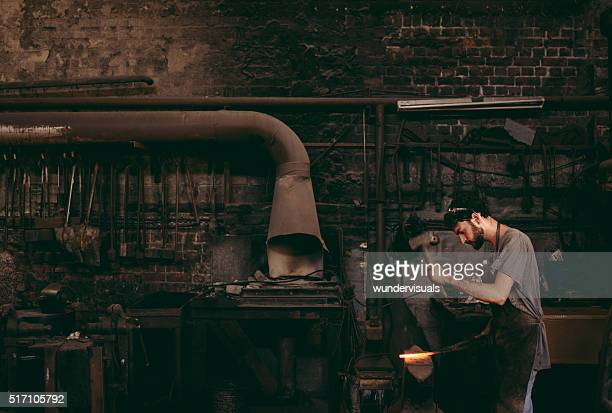 Blacksmith hammering glowing iron on anvil in workshop