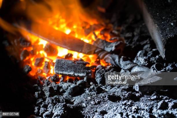 Blacksmith Heating Metal Over Coal Fire