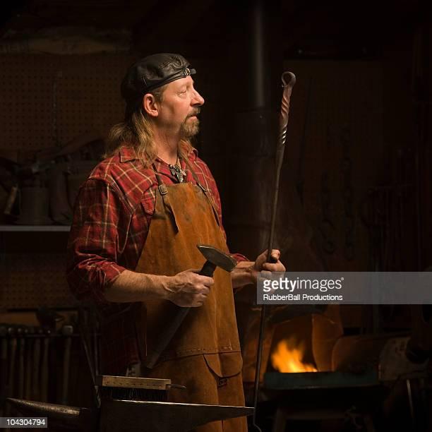 Fabbro ferraio che tiene un martello