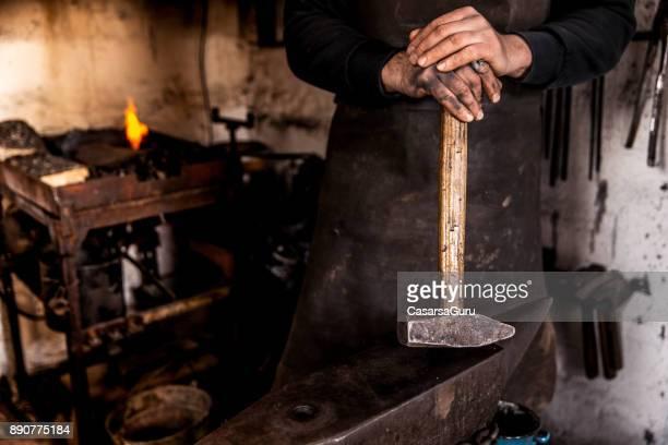 Halten einen eisernen Hammer am Amboss Schmied