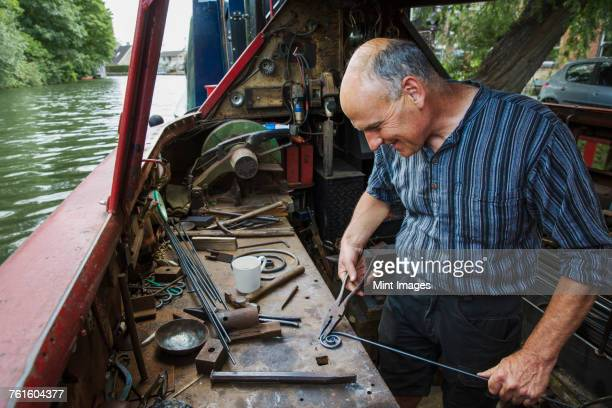 Blacksmith in his floating workshop on a narrowboat, holding pliers and metal rod, working a metal object.