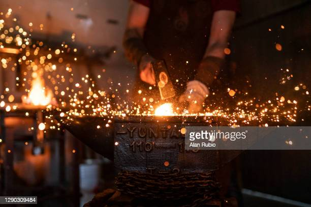 blacksmith in his workshop forging his new creation. - skill stock pictures, royalty-free photos & images