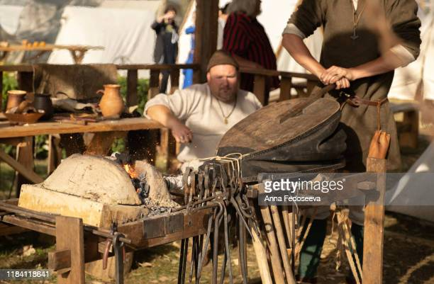 a blacksmith inflates a flame with blacksmith furs. blacksmith forge. inflate furs. reconstruction of old crafts. middle ages role-playing historical games. master blacksmith. metal tools. clamp. - rpg maker stock pictures, royalty-free photos & images