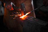 Blacksmith manually forging the molten metal
