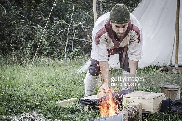 A blacksmith operating the bellows to stoke the forge fire in a Langobard camp Northern Italy 6th century Historical reenactment