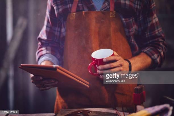 smid, lezen van e-mails op tablet en drinken koffie in workshop - handwerkprodukten stockfoto's en -beelden