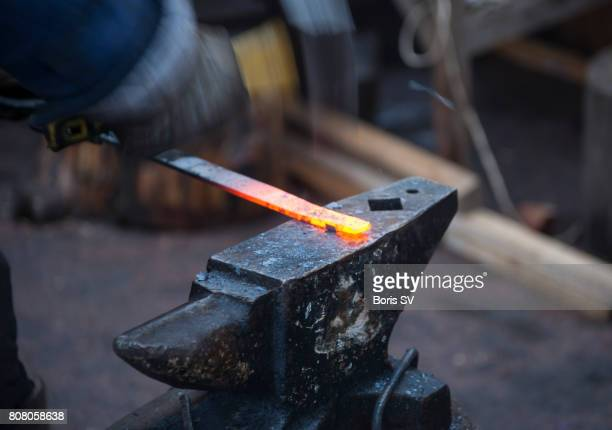 A blacksmith shaping a hot piece of iron on an anvil with a hammer