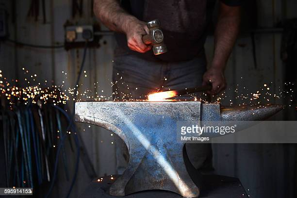A blacksmith shaping a hot piece of iron on an anvil with a hammer, with sparks flying.