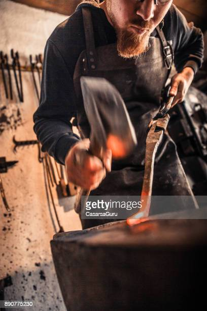 blacksmith shaping iron for knife handle with a hammer - strike industrial action stock pictures, royalty-free photos & images