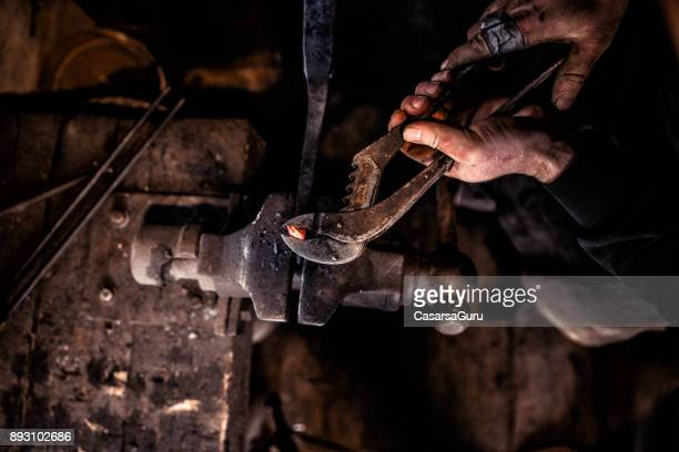 Blacksmith Shaping Metal Head Of Ram Using The Forge Tongs