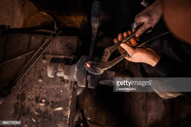 Blacksmith Shaping Molten Iron with Locking Pliers Directly Above