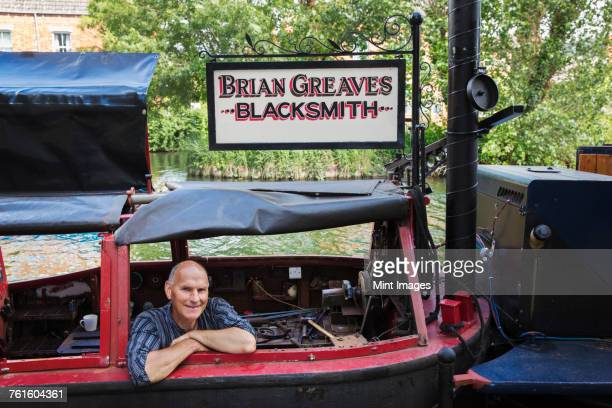 Blacksmith sitting on his working narrowboat on a waterway, looking at camera, smiling.