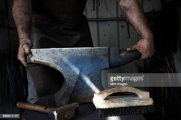 Blacksmith standing at an anvil in a traditional forge.