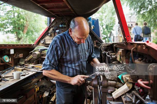 Blacksmith standing in his workshop, a floating forge on a narrowboat barge, working on a metal object, using a file.