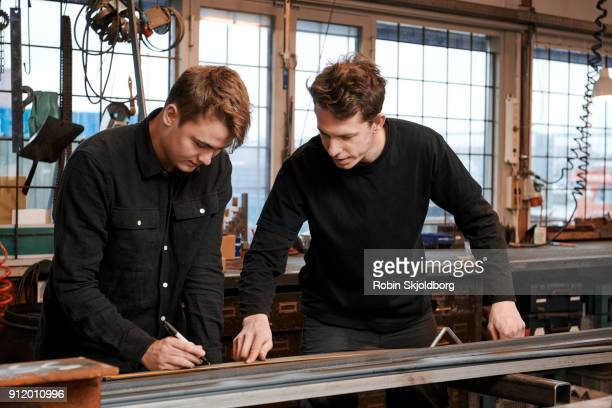 blacksmith teaching student in workshop - robin skjoldborg stock pictures, royalty-free photos & images