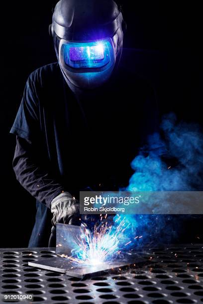 blacksmith wearing protective mask welding in workshop - robin skjoldborg stock pictures, royalty-free photos & images