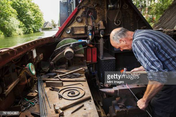 Blacksmith working in a small space on his narrowboat, a barge on river, bending over the anvil and shaping hot metal.